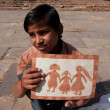 Boy shows his naive drawing of the happy family — Stock Photo