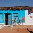 Traditional indian house of blue color with a bicycle — Stock Photo