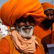 Elderly indian pilgrim in orange turban on the celebration Kumbh Mela - Stock Photo