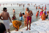 Senior man comes out from the water of sacred Sangam — Stock Photo