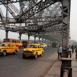 Stock Photo: Yellow Ambassador taxi cabs goes on Howrah bridge