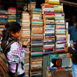 Young female student choose the book on the street market — Stock Photo #21962137