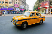 Yellow Ambassador taxi car goes through the street — Stock Photo