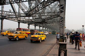 Yellow Ambassador taxi cabs goes on the Howrah bridge — Stock Photo