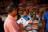 Customer and book trader on the asian street market — Stock Photo