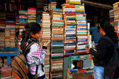 Young female student choose the book on the street market — Stock Photo