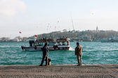 Senior men fishing from the pier Beyoglu at sunset — Stock Photo