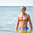 Stock Photo: Semi nude handsome smiling mstanding in sea