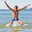 Stock Photo: Semi nude handsome mjumping in sea