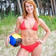 Pretty girl posing with the ball on the beach — Stockfoto