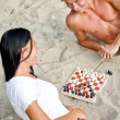 Royalty-Free Stock Photo: Young couple playing chess on the beach