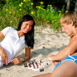 Young couple playing chess on the beach — Stock Photo