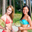 Two girls posing with badminton rackets on the beach — Stock Photo