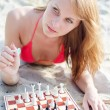 Portrait of pretty woman playing chess on the beach — Stock Photo