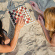Two girls playing chess on the beach — Stock Photo