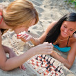 Two girls playing chess on the beach — 图库照片