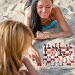 Stock Photo: Two girls playing chess on the beach