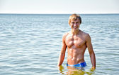 Semi nude handsome smiling man standing in the sea — Stock Photo