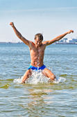 Semi nude handsome man jumping in the sea — Stock Photo
