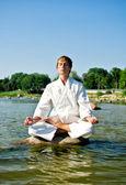 Man in kimono meditating on the rock in the sea — Stock Photo