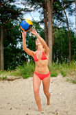 Young woman playing volleyball on the beach — Stock Photo