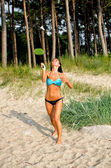 Pretty woman playing badminton on the beach — Stock Photo