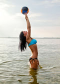 Young woman playing volleyball in the sea — Stock Photo