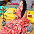 Stock Photo: Young Indigirl in traditional red clothing with Hookah
