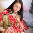 Young Indian girl in traditional red clothing with Hookah -  