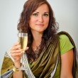 Girl in traditional green clothing with glass of champagne — Stock Photo