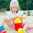 Little girl playing with toys on the beach — Stock Photo #12176799