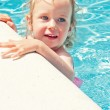Cute little girl having fun in the swimming pool — Stock Photo