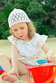 Little girl playing with toys on the beach — Stock Photo