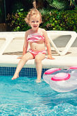 Cute little girl sitting near the swimming pool — Stock Photo