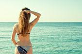 Woman in bikini rotated back looking at sea panorama view — Stock Photo
