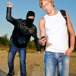Bandit in mask trying to rob young man — Stock Photo