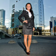 Pretty woman posing in front of modern office building — Stock Photo