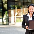 Stock Photo: Businesswoman with notebook in front of office building