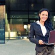 Businesswoman with notebook in front of office building — Stock Photo