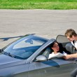 Male thief stealing handbag from the car while his accomplice distracts fem — Stock Photo