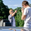 Bandit with a gun threatening young man near the car — Stock Photo