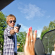 Bandit with a gun threatening young woman in the car — Stock fotografie #12308280