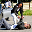 Стоковое фото: Male thief stealing a car while his accomplice distracts female driver