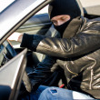 Stock Photo: Bandit in mask stealing car.