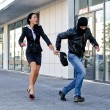 Stock Photo: Bandit stealing businesswoman bag in the street
