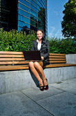 Businesswoman with notebook in central city park — Stock Photo