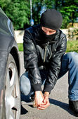 Man in mask punctures a car tyre. Revenge concept — Stock Photo
