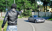 Man in mask pointing gun toward car. Robbery concept — Stock Photo