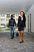 Bandit in mask following businesswoman. Robbery concept — Stock Photo