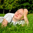 Young woman relaxing on the grass in park — Stock Photo #12367440